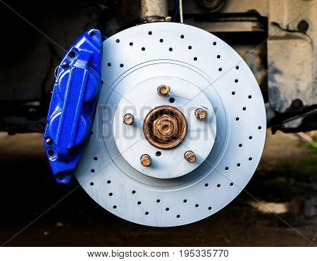Blue brake caliper with perforated disk in workshop