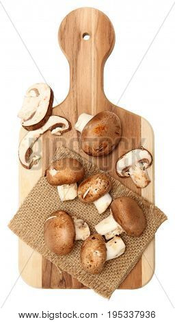 Baby Bella Mushrooms whole and sliced unwashed on cutting board.