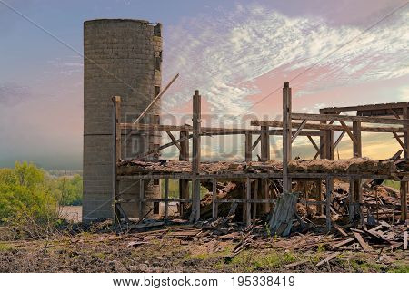 cement block silo with pile of rubble from wooden barn