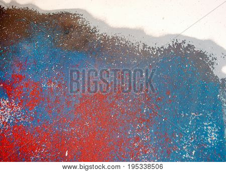 close up view of red and blue painted abstract design on coarse metal surface