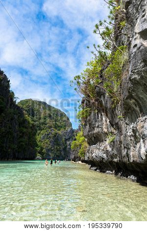 EL NIDO PALAWAN PHILIPPINES - JANUARY 17 2017: Vertical picture of sharp rocks with blue sky in the exotic Lagoon in El nido.
