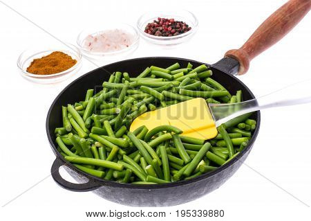 Cut into pieces of green beans in frying pan on white background. Studio Photo