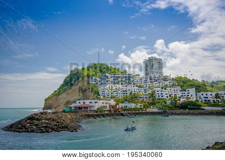 Beautiful rocky beach with a buildings structure of hotels behind in a beautiful day in with sunny weather in a blue sky in Same, Ecuador.
