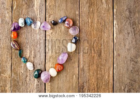 Tumbled healing crystals in heart shape on wooden plank background