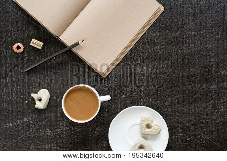 Cup of coffee, diary with empty brown pages, a black pencil with a sharpener and a plate with three heart-shaped cookies on a black shabby background.