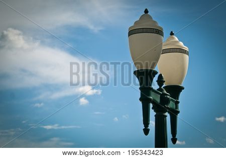 Low angle view of classic lighting pole against blue sky