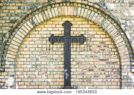 old metal cross on brick wall background - rusty cross on grave
