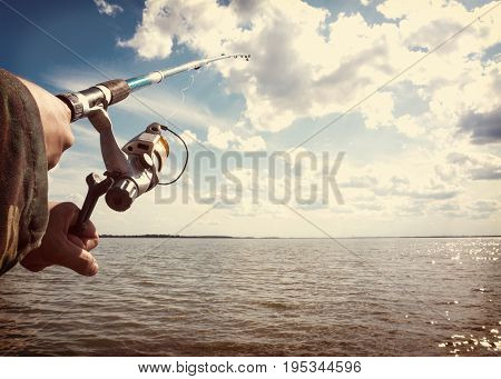 Human Hands Holding A Fishing-rod