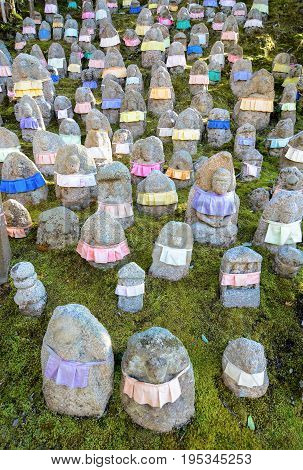 Japanese Jizo statues to remember deceased children. The aprons provide cloth for Jizo's robe to protect the children in the afterlife.