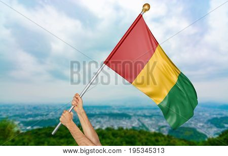 Young man's hands proudly waving the Guinea national flag in the sky, part 3D rendering