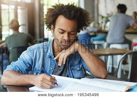 Headshot Of Serious Dark-skinned Graduate Student In Blue Stylish Shirt Studying At Canteen Or Cowor
