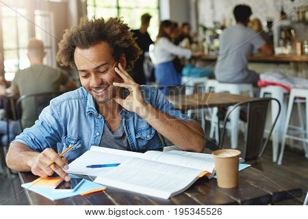 Waist Up Portrait Of Positive Smiling Afro American College Student Typing Text Message On His Smart