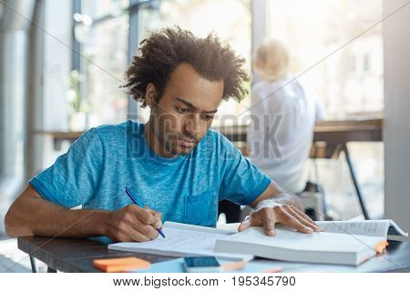 Concentrated Young Student Male In Blue T-shirt Sitting At Desk Indoors Rewriting Information From B
