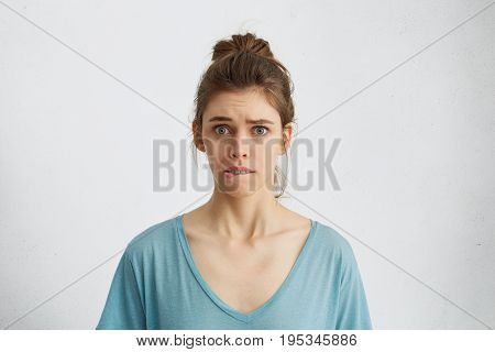 Young Female Having Worried Look Biting Her Lower Lip Nervously Looking With Her Blue Anxious Eyes I