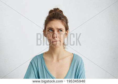 Portrait Of Doubtful And Pensive Woman Looking Up And Curving Her Lips Trying To Make Decision. Irre