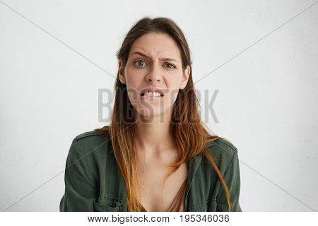Displeased Young Pretty Woman Curving Her Lips, Biting With Teeth, Frowning Face Looking With Disapp