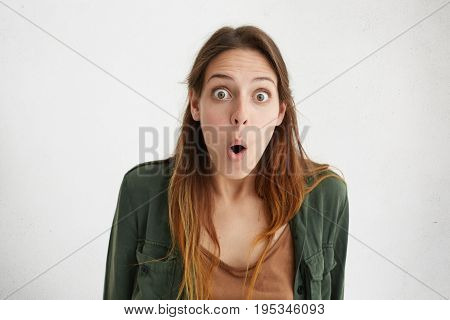 Studio Shot Of Amazed Woman With Bugged Eyes And Opened Mouth Staring In Camera After Hearing Latest