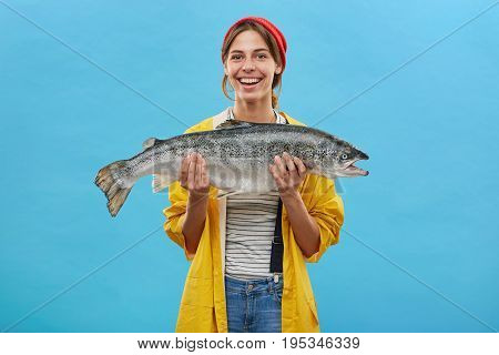 Glad Fisher Woman In Yellow Anorak And Jeand Overalls Holding Huge Fish Rejoicing To Catch It Demons
