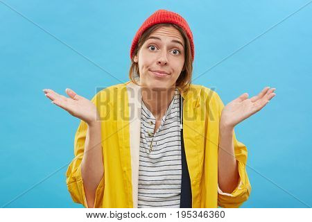 Clueless Teenage Girl Wearing Red Stylish Hat And Yellow Raincoat Staring At Camera With Wide-eyed E