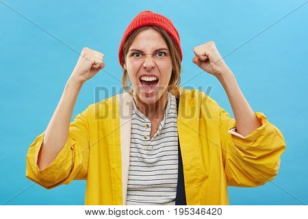 Portrait Of Happy Successful Young Caucasian Woman Winner Wearing Red Hat And Yellow Raincoat Rejoic