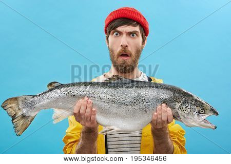 Headshot Of Funny Emotional Young Bearded Caucasian Fisherman In Hat And Raincoat Holding Large Salm