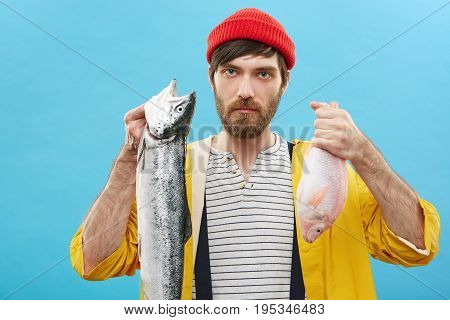 Attractive Unshaven Young Male Fishmonger Holding Two Fish In His Hands After Deep-sea Fishing, Offe