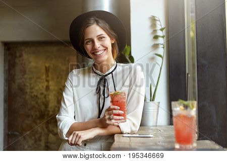 Beautiful Elegant Lady Wearing Black Hat, White Blouse And Trousers Standing In Cafe Holding Red Fre