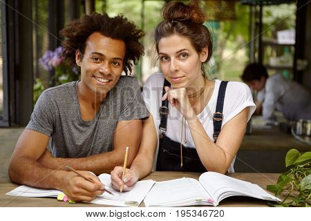 Handsome Black Male Student And Attractive Female With European Appearance Working Together Writing
