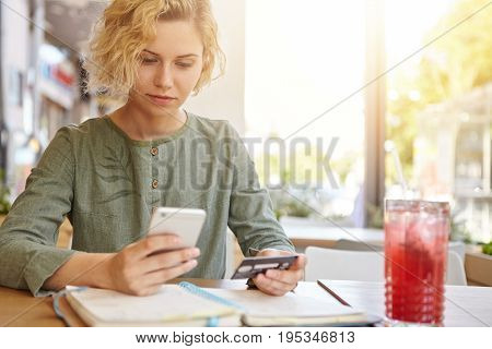 Elegant Blonde Woman In Blouse Sitting At Cafe Holding Mobile Phone And Plastic Card Signing Up On W