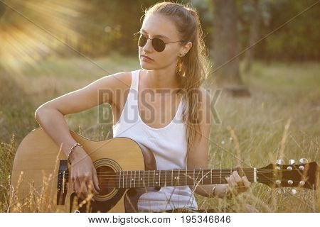 Beautiful Female With Pony Tail Dressed In White T-shirt Playing Guitar While Sitting Alone On Green
