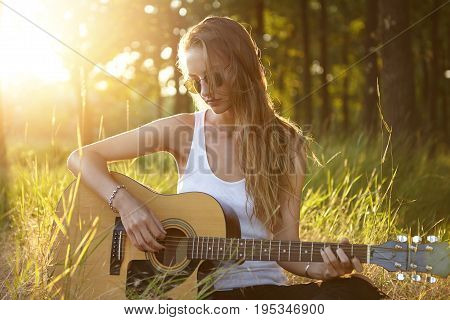 Pretty Female With Dark Long Hair Feeling Relaxed While Sitting At Green Grass In Forest Playing Gui