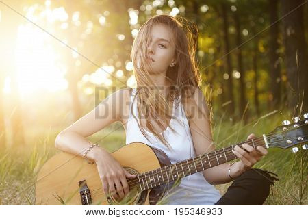 Stylish Female With Long Hair Relaxing At Sunlight In Beautiful Forest Playing Musical Instrument Wi