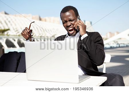 Angry African American Businessman Sitting At Outdoor Cafe In Front Of Open Laptop, Talking On Cell