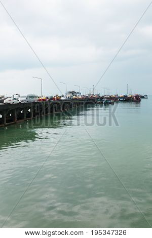 Passenger Pier With Many Cars And Boats