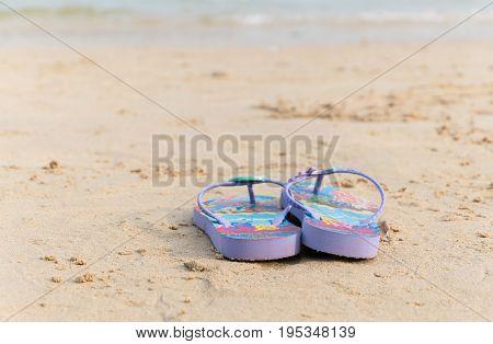 purple flipflop on beautiful sand beach background