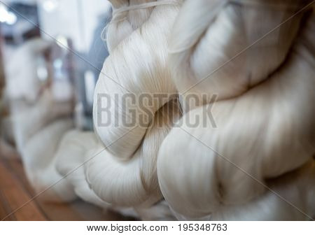 Suzhou, China - Nov 5, 2016: At Suzhou Number 1 Silk Factory; soft silk threads bundled into strong rope format. Low-light and shallow depth of field image.