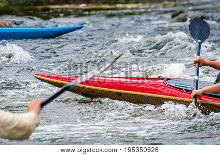 The nose of the kayak and the oars are close-up. Rafting on river rapids.