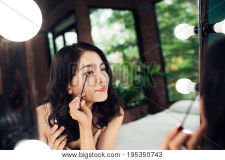 Portrait of beautiful young woman looking at the mirror applying black mascara on eyelashes at home
