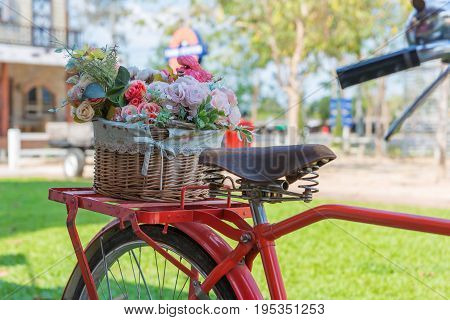 Vintage Bicycle Equipped With Basket Of Flowers In The Garden
