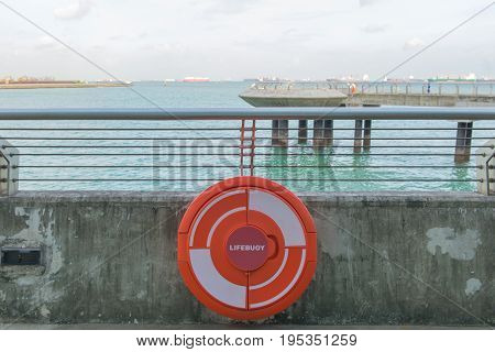 red Lifebuoy on railing by the sea.
