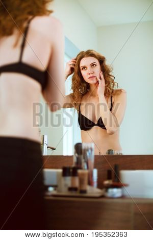 Young woman looking herself in the mirror on bathroom.