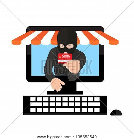 Man wearing balaclava and holding credit card while using laptop at desk