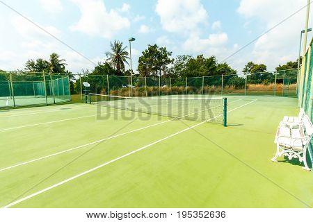 Outdoor tennis court, no green grass field.