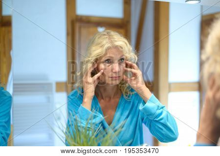 Senior Woman Checking Her Wrinkles In A Mirror