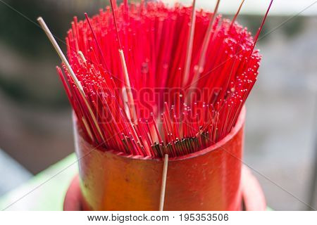 Red Incense sticks in joss stick pot