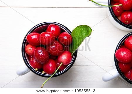 Cherry In Enamel Cup On White Wooden Background. Healthy, Summer Fruit. Cherries. Top View.