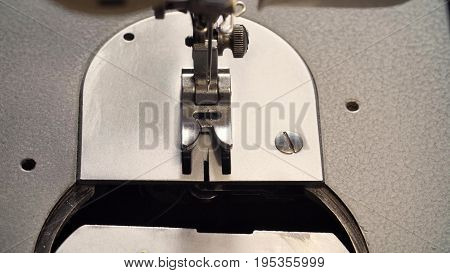 Extreme close up of inserting a bobbin in the sewing machine