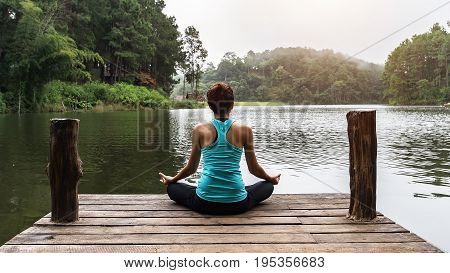 Close up hand. Woman do yoga outdoor. Woman exercising yoga at the nature background select focus
