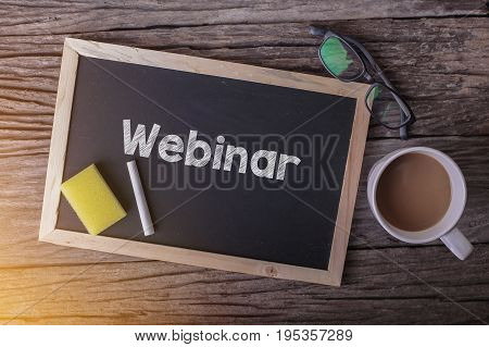 Webinar On Blackboard With Cup Of Coffee, With Glasses On Wooden Background.