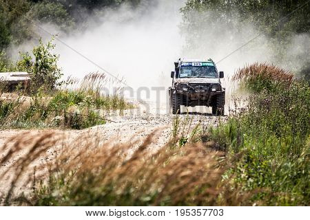 Heavy Off-road Racing Car Driving Along The Dusty Road.